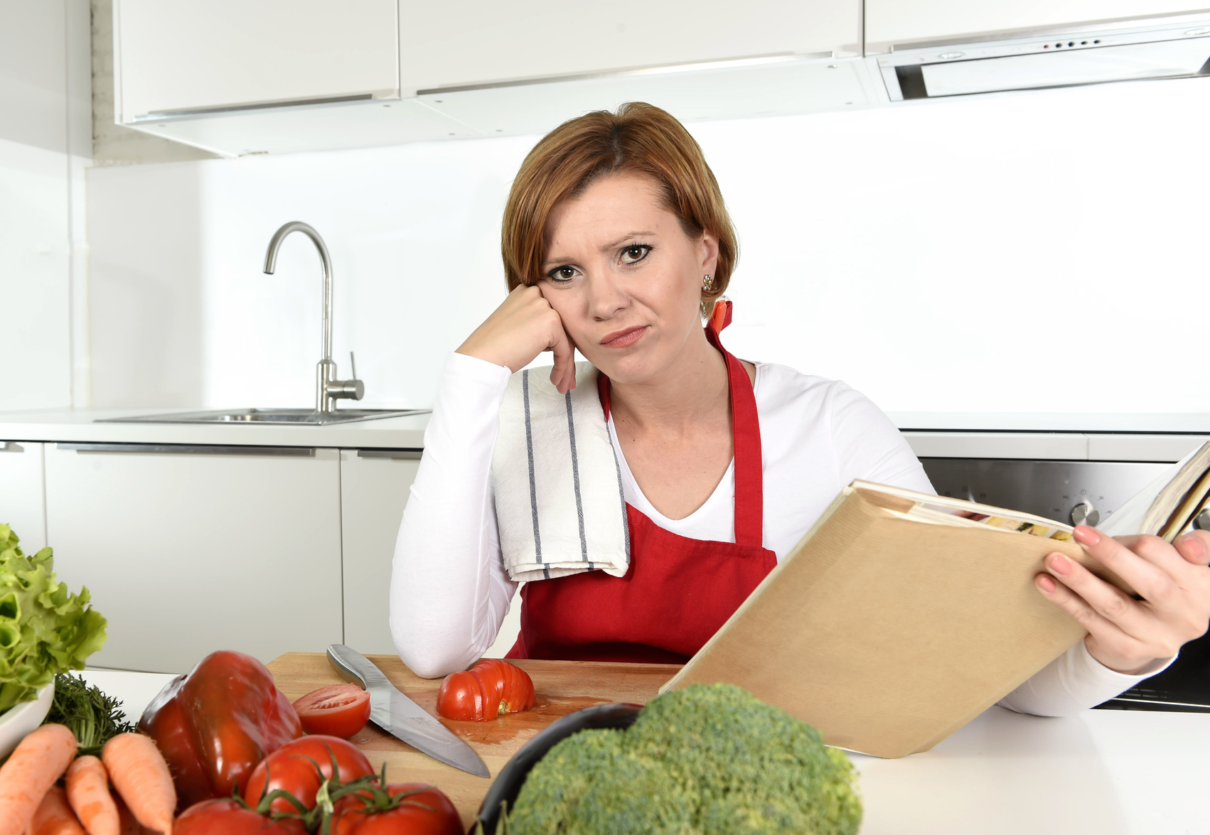 upset cook woman bored and frustrated reading recipes book in home ...